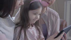 Grootmoeder, moeder en weinig dochterzitting samen op de bank in moderne flat Het gadget van de meisjesholding, mamma stock video