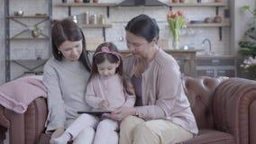 Grootmoeder, moeder en weinig dochterzitting samen op de bank in moderne zitslaapkamer Het gadget van de meisjesholding stock video