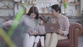 Grootmoeder, moeder en weinig dochterzitting samen op de leerbank in moderne zitslaapkamer Iedereen heeft stock footage