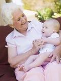 Grootmoeder in openlucht op terras met baby royalty-vrije stock afbeeldingen