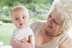 Grootmoeder in openlucht op terras met baby Stock Fotografie