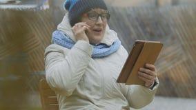 Grootmoederbesprekingen op telefoon en gebruikstablet in openlucht stock video