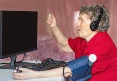 Grootmoeders in de moderne wereld van geavanceerd technisch De grootmoeders houden computer van spelen stock afbeelding