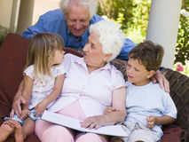 Grootouders die aan kleinkinderen lezen Stock Fotografie
