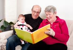 Grootouders die boek lezen aan babymeisje Royalty-vrije Stock Fotografie