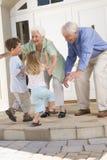 Grootouders die kleinkinderen welkom heten stock afbeeldingen