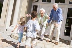 Grootouders die kleinkinderen welkom heten stock fotografie