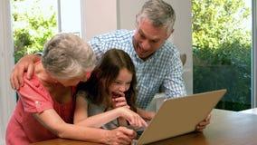 Grootouders die laptop met kleindochter met behulp van stock video