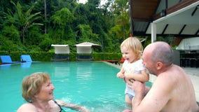 Grootouders die met babymeisje spelen in zwembad stock videobeelden
