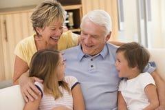 Grootouders die met kleinkinderen lachen royalty-vrije stock afbeeldingen