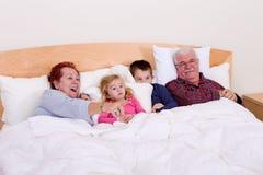 Grootouders die op TV in het bed met hun Grote jonge geitjes letten Stock Foto