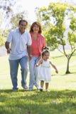 Grootouders die in park met kleindochter lopen Stock Foto