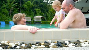 Grootouders en babymeisje het spelen in zwembad stock footage