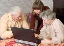 Grootouders en kleindochter die aan lapt kijken Royalty-vrije Stock Foto's