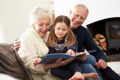 Grootouders en Kleindochterlezingsboek thuis samen royalty-vrije stock afbeelding