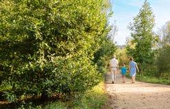 Grootouders en kleinkind die in openlucht lopen Stock Foto's