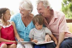 Grootouders en Kleinkinderen die Boek op Tuin Seat lezen Stock Afbeelding