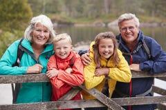 Grootouders en kleinkinderen die op een houten omheining in het platteland leunen die, Meerdistrict, het UK lachen stock foto