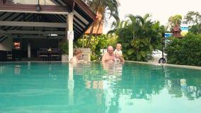 Grootouders met kleindochter in zwembad stock video