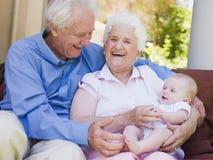 Grootouders in openlucht op terras met baby royalty-vrije stock afbeelding