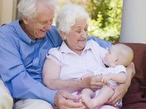 Grootouders in openlucht op terras met baby Royalty-vrije Stock Afbeeldingen