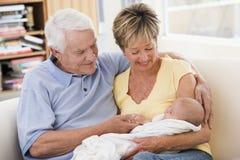 Grootouders in woonkamer met baby Royalty-vrije Stock Afbeeldingen
