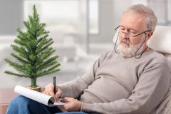 Grootvader die de het winkelen lijst voor de wintervakantie maken Stock Foto