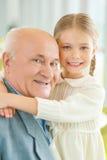 Grootvader die grote tijd met weinig kleindochter hebben royalty-vrije stock foto