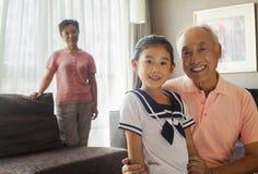 Grootvader die haar kleindochter, grootmoeder op de achtergrond houden Stock Foto's