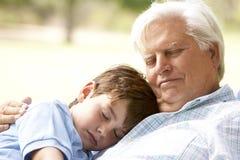 Grootvader die Kleinzoon in Park koestert Stock Afbeelding