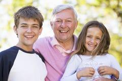 Grootvader die met kleinkinderen lacht Royalty-vrije Stock Foto's