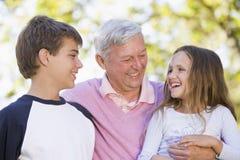 Grootvader die met kleinkinderen lacht Stock Fotografie