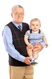 Grootvader die zijn kleinzoon houdt Stock Afbeelding