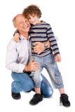 Grootvader die zijn kleinzoon omhelst Stock Afbeelding