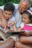 Grootvader en jonge geitjes die boek lezen Royalty-vrije Stock Foto's