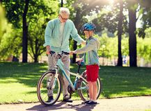 Grootvader en jongen met fiets bij de zomerpark royalty-vrije stock afbeeldingen