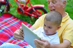 Grootvader en kind in park die tablet gebruiken Stock Foto