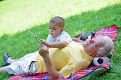 Grootvader en kind in park die tablet gebruiken Royalty-vrije Stock Afbeelding