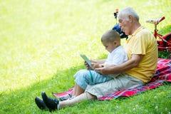 Grootvader en kind in park die tablet gebruiken Stock Afbeelding