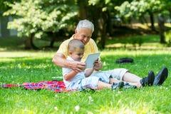 Grootvader en kind in park die tablet gebruiken Stock Afbeeldingen