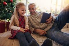 Grootvader en kleindochter die een video op digitale tablet D hebben Royalty-vrije Stock Afbeeldingen