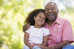 Grootvader en kleindochter die in openlucht glimlachen Stock Fotografie