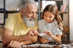 Grootvader en kleindochter die twee puzzelstukken verbinden royalty-vrije stock fotografie