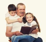 Grootvader en kleinkinderen gelezen boek Stock Afbeeldingen