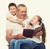 Grootvader en kleinkinderen gelezen boek stock afbeelding