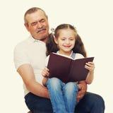 Grootvader en kleinkinderen gelezen boek stock fotografie