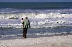 Grootvader en kleinzoon bij strand stock foto
