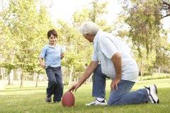 Grootvader en Kleinzoon die Amerikaanse Voetbal spelen Royalty-vrije Stock Afbeelding