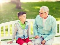 Grootvader en kleinzoon die bij de zomerpark spreken stock foto's