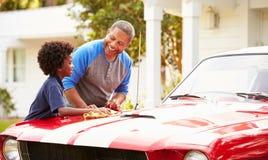 Grootvader en Kleinzoon die Herstelde Klassieke Auto schoonmaken Royalty-vrije Stock Foto's